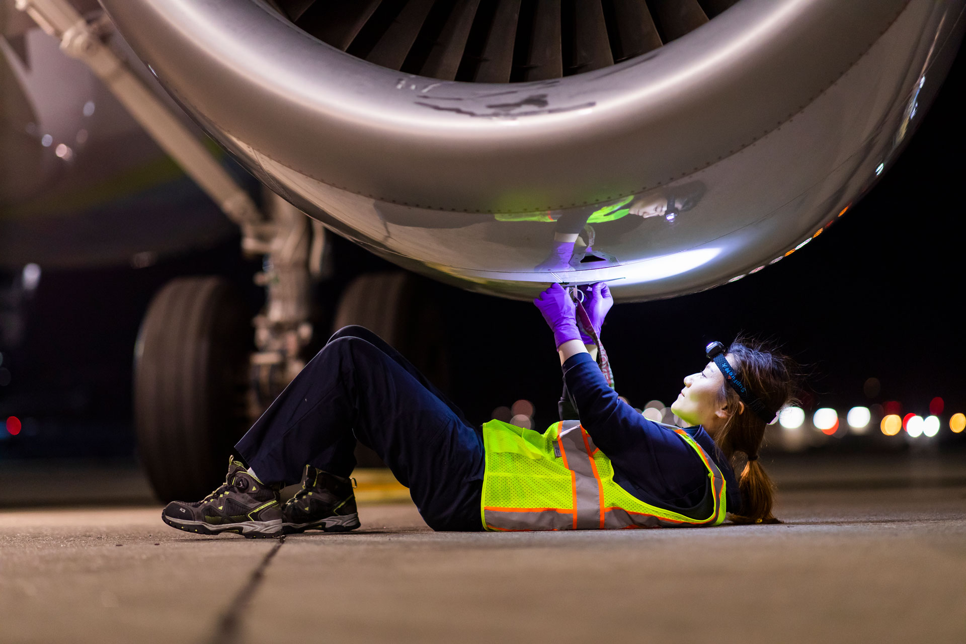 Woman with a wrench in front of a jet turbine