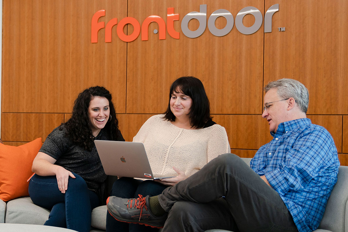 Life at Frontdoor. 2 women and 1 man looking at a laptop while sitting on a couch at Frontdoor