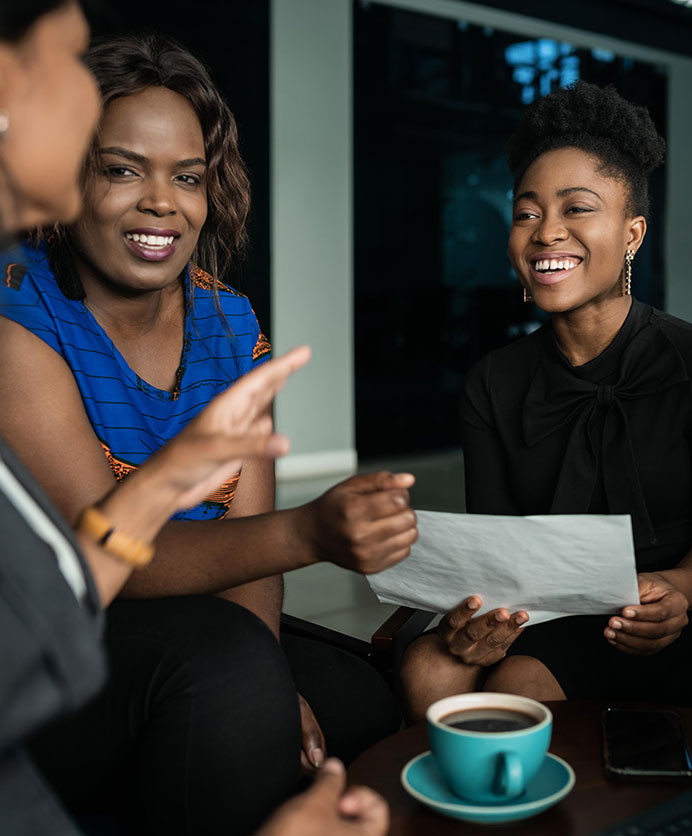 Young African businesspeople going over paperwork during a casual meeting in an office